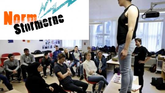 En underviser fra Normstormerne står på bordet i en skoleklasse, som en den af en øvelse.