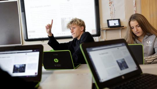 Billede af skoleelever i klassen med computer