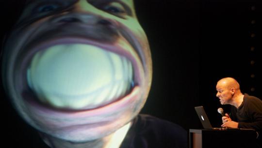Billede af Thomas Sandberg der smiler ind i et webcam, og smilet projekteres stort op på skærm bag ham.
